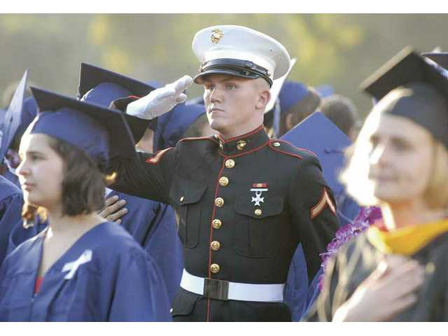 Nicholas Laccabue, who graduated wearing his U.S. Marine Corps. uniform, snaps to attention during the National Anthem at the Saugus High School graduation ceremony at College of the Canyons on Wednesday.