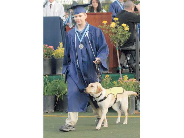 "Saugus High graduate Karlen English receives his diploma as he walks with ""Jennarae,"" a 9-month-old yellow Labrador Retriever that he is training as a seeing eye dog."