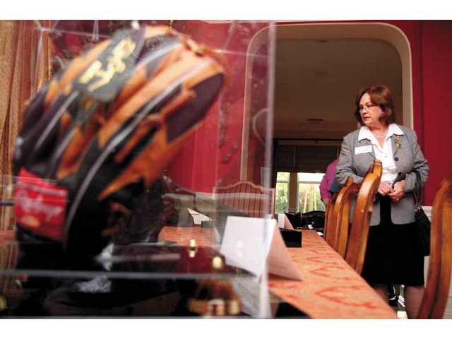 Elizabeth Hopp, of Valencia, walks through the Fleming home on May 29, looking over at some of the auction items previewed at the party. In the foreground is the autographed glove of Tony Gwynn. Because the party's theme is sports, many of the previewed items were sports-related.
