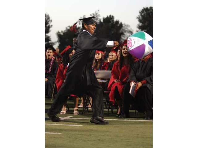 Jose Arello, 1, kicks a beach ball during the Hart High School graduation, Wednesday evening at COC Cougar Stadium.