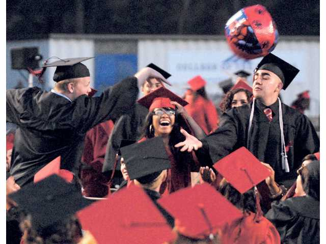 From left, Hart High School graduates Bob Caprine, Yessica Diego and Emilio Carrillo bat a beach ball after receiving their diplomas during graduation ceremonies at College of the Canyons on Thursday.