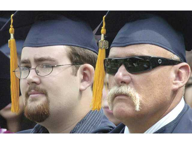 Son, Cameron, left, and father Rus Shaaban listen to speeches as they wait to receive their diplomas together at Collece of the Canyons graduation ceremonies on Friday.