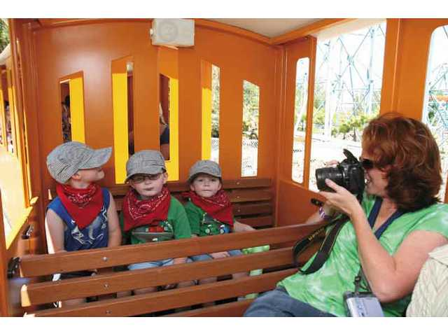 Melissa Stradre photographs her three sons, Austin, 5, Tyler, 3, and Logan, 2, on the train at Six Flags on Thursday morning.