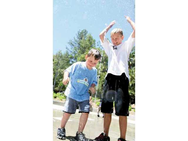 Charlie Tomlin, 10, from Mojave (right) and Zackary Harris, 3, from Santa Clarita, play around in the ground water fountain area of Thomas Town Thursday morning.