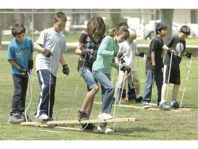 "Two Meadows Elementary School teams race in a game called ""Mountains and Rivers,"" which is designed to teach the teamwork used by the Lewis and Clark Expedition to overcome the obstacles of its cross-country trek during the early 19th century, at Valencia Meadows Park on Friday for the school's Lewis and Clark Day."