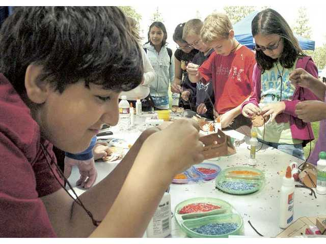 Meadows Elementary School fifth-grader Gregory Hovanessian, left, sews a pair of paper moccasins as his group learns about Native American folklore in a learning exercise about the Lewis and Clark expedition at Valencia Meadows Park on Friday.