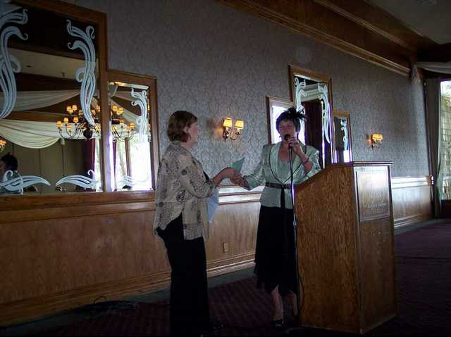 Sally Coss, president of the Xi Nu Zeta sorority, presents Judy Riley with the group's annual check for the Santa Clarita Valley Scholarship Foundation.
