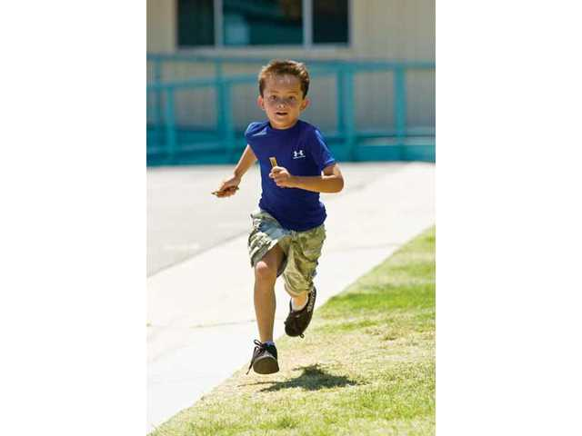 Second-grader Ethan Bain runs around the Castaic Elementary School field to help raise funds for Children's Hospital of Los Angeles. When the school year started, students were asked how many miles they would run to help raise the funds, and Friday was the last day for them to run. Ethan has run more than 40 miles this year.