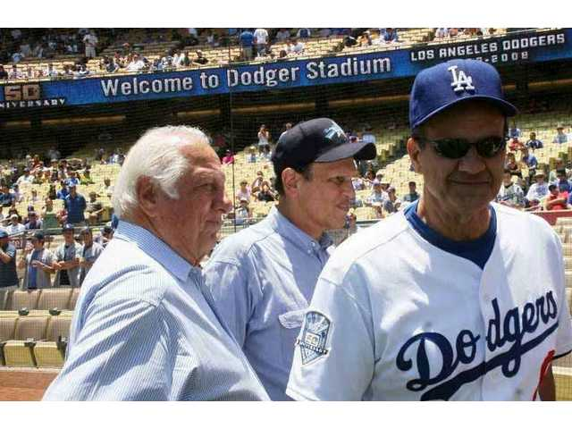 Former Dodgers manager Tommy Lasorda, financier/philanthropist Michael Milken and current Dodgers manager Joe Torre are pictured on the field Saturday, SCV Dodger Day at Dodger Stadium.