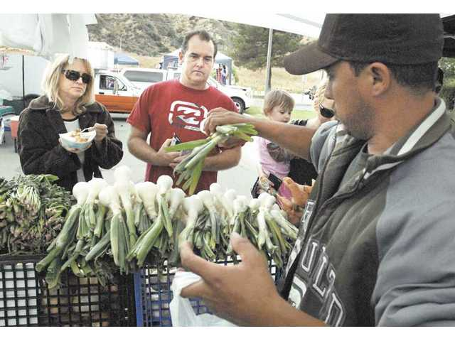 Armando Contreras, right, of Doctor Farms, bags sweet onions for Sue and Paul Henderson of Castaic at the Castaic Farmers Market on Saturday.