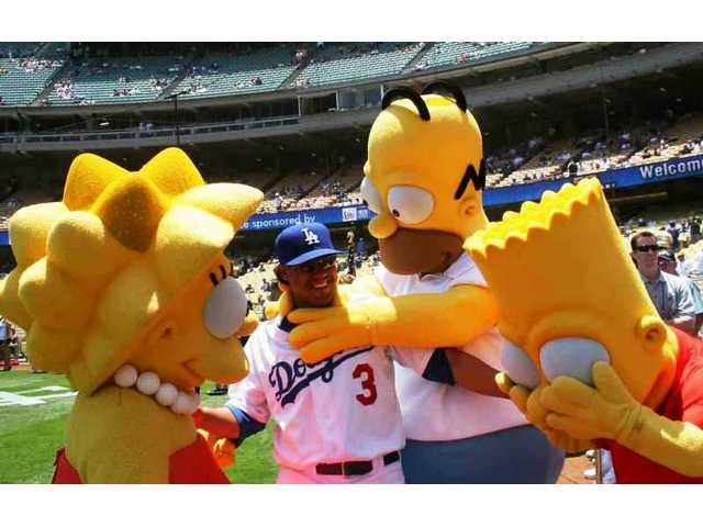 Before the game against the Cubs Saturday afternoon at Dodger Stadium, versatile young Dodger Delwyn Young gets worked over by Homer Simpson as Lisa looks on and Bart covers his eyes in disbelief. The characters were at the stadium to plug a new Universal Studios attraction.
