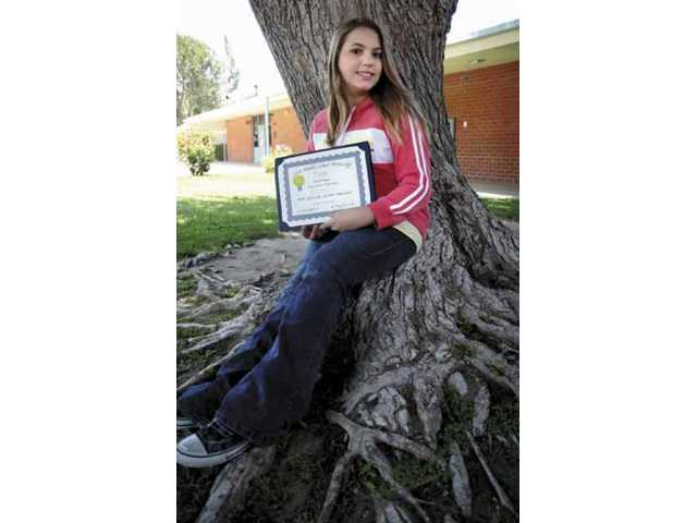 Sierra Vista Junior High eighth grade student Maral Sakayan, 14, shows off the first-place award she received in a county-wide essay competition.