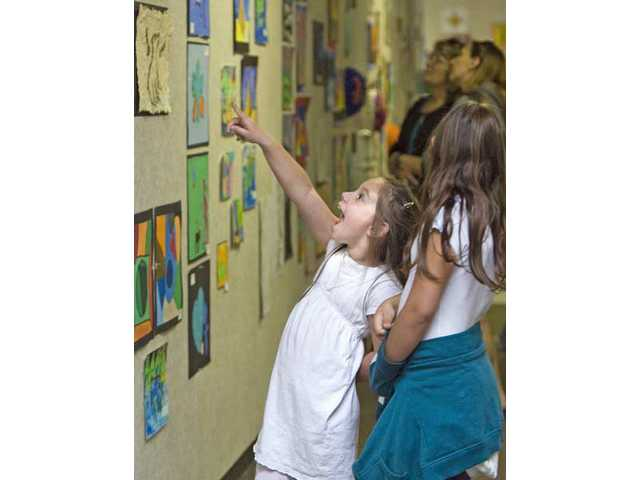 Kamryn Hochberg, 5, and sister McKenzie, 9, walk around Valencia Valley Elementary School during the annual student art show Monday evening.