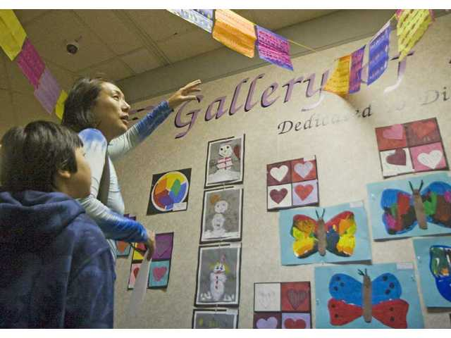 Akiko Stamer and son Teddy, 8, look at art at the annual Student Arts Show on display at Valencia Valley Elementary School Monday.