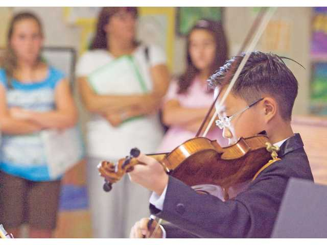 "Violinist 11-year-old Christian Chung of Stevenson Ranch Elementary School plays ""Lullaby"" during the Student Art Show at Valencia Valley Elementary School Monday evening."