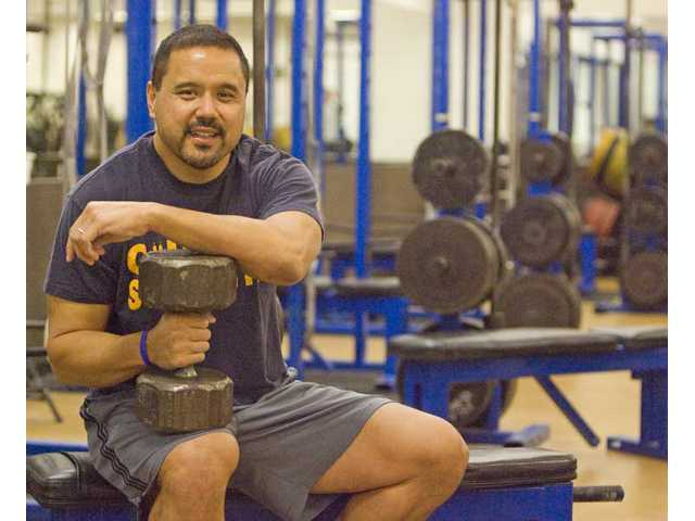 College of the Canyons strength and conditioning coach Robert dos Remedios holds a dumbbell in the school's weightroom on Tuesday. dos Remedios has helped many COC athletes get into superior shape over the years.