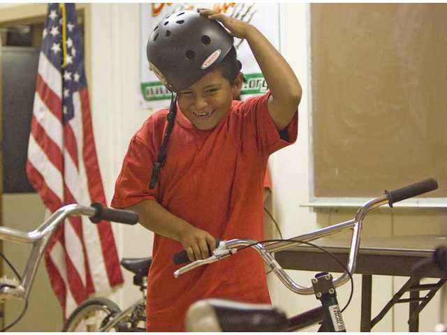 After completing the five-week Bicycle Education and Registration program, 7-year-old Angel Cruz graduates Wednesday afternoon at Val Verde Park. Kids who completed the program received a helmet, a T-shirt, a certificate and a new bike to take home.