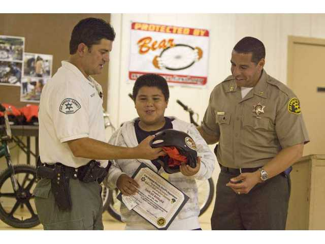 Deputy Brian Rooney, left, along with sheriff's Captain Anthony La Berge, hand Carlos Barajas his graduation certificate, a helmet and a T-shirt for completing the five-week Bicycle Education and Registration program.