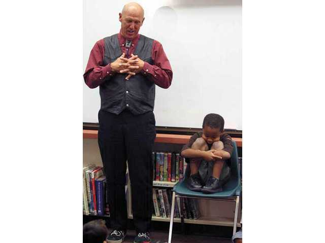 Story teller James Cogan tells the story of Barney Bear, portrayed by Canyon Springs Elementary's Kani Weston, right, on Tuesday morning.  The story was written and illustrated by the school's kindergarten classes and won the Grand Prize in a Time Warner Cable contest.
