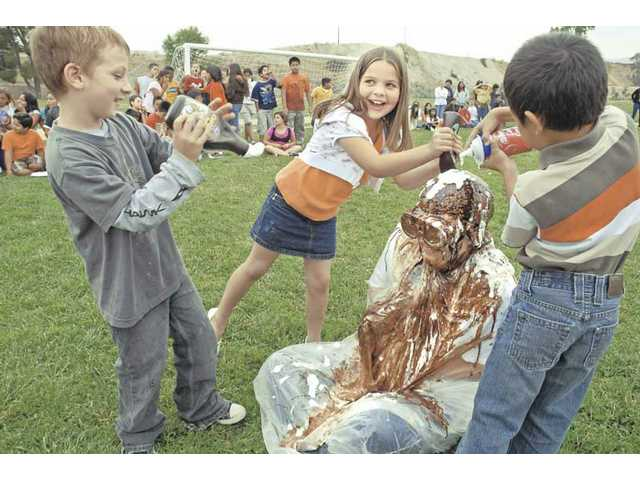 Mint Canyon Elementary School second-grade teacher Marina Hubbard drips with chocolate syrup and marshmallows on Wednesday.