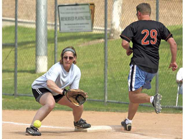 Mitch Zippay readies for a low throw as a Villain reaches first base safely. Zippay said she had been playing softball at Central Park since 2004.