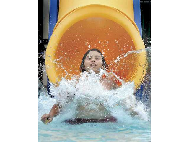 Saul Andrade, 11, tries out the new slide at Newhall Park pool on Friday. The pool will be open today and Sunday from 1 p.m. to 4 p.m.
