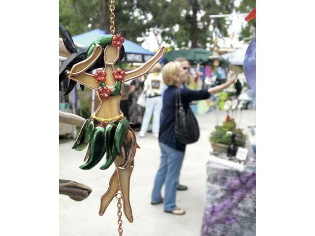 A hula dancer wind chime hangs with other handmade creations at the Weathered Woods booth as shoppers visit the Fine Craft Show at Old Orchard Park on Saturday.