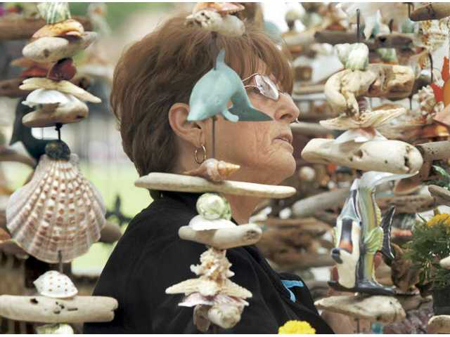 Sandy Taylor, of Valencia, looks at the handmade creations at the Weathered Woods booth at the Fine Craft Show at Old Orchard Park on Saturday.