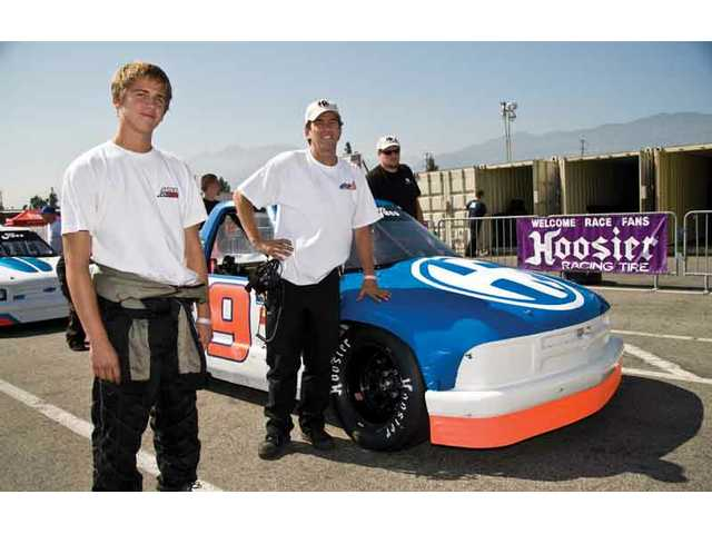 Valencia graduate Connor Cantrell, left, stands next to his father, Jim, before a race on Saturday in the garage at Toyota Speedway at Irwindale.
