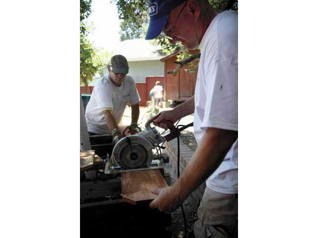 Jeff Hyde, volunteer from Lowes (front) and Jim McInerney, volunteer from The Gas Company, cut pieces of wood for patch work in the backyard fence of the Tindell home in Newhall Saturday morning.