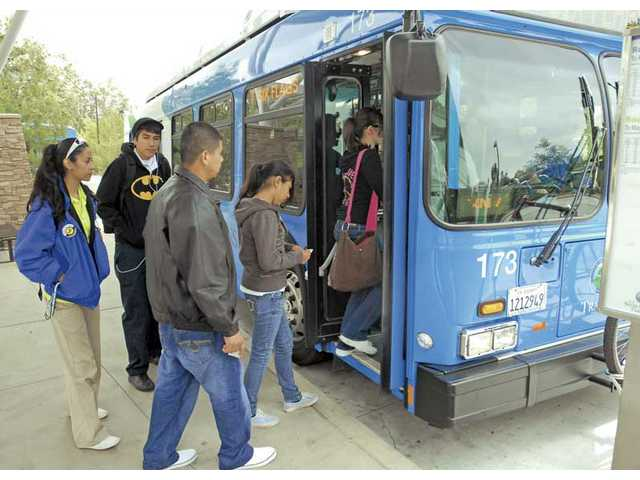 Commuters get on a bus at the Valencia transfer station on Valencia Boulevard on Thursday.