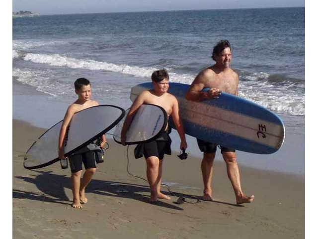 From left: Will, Peter and Eric Christiansen get ready to surf at a local beach. Will recently made his father proud when he saved a swimmer from drowning at Bolsa Chica State Beach in Huntington Beach.