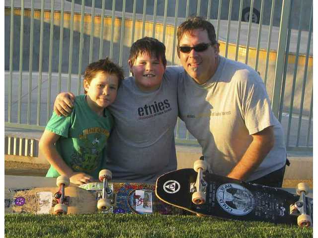 Will Christiansen, 8, left, and brother Peter, 10, center, hang with their father, Eric, after a shred session at a Glendale skate park.
