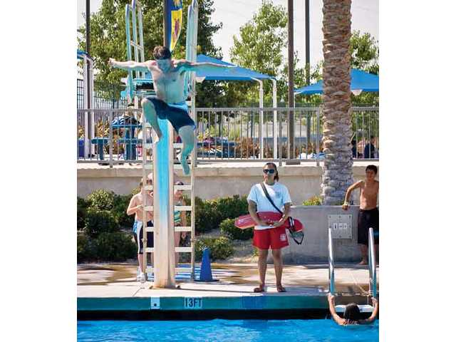 Sean Albertson of Valencia jumps off the high diving board at the Santa Clarita Aquatic Center, as his three children and two step-children root for him in the pool. Albertson was one of many local fathers trying to cool off from the warm summer-like weather at the swimming pool on Father's Day.