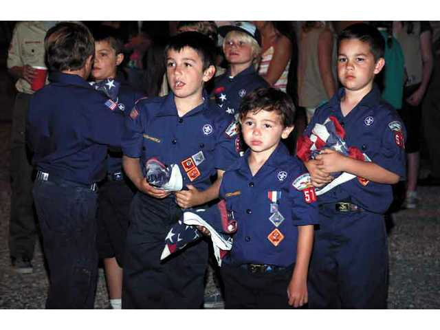 Cub Scouts from pack 575 in Saugus watch as fellow Scouts take turns burning retired flags Friday night at the Elks Lodge flag retirement ceremony.