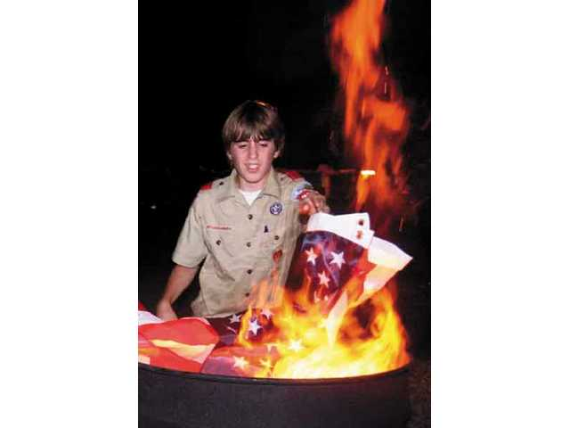 Spencer Saunders from troop 2379, Canyon Country, carefully places an old flag to burn, during a flag burning ceremony at the Elks Lodge, Friday night.