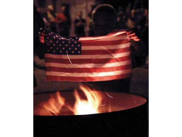 John Hamburger holds the American flag by the fire before throwing it into the fire pit, Friday night at the Elks Lodge.