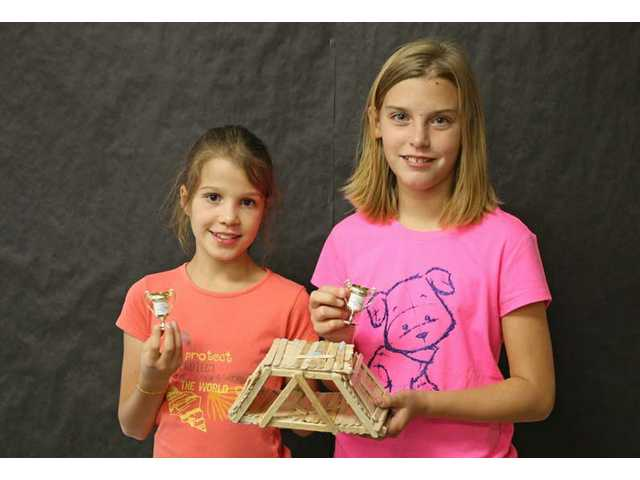 "Winning bridge-builders Claire Williams and Margaux Chotel hold the winning bridge, ""The Leaning Bridge of Popsicle Sticks."""