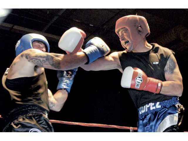 Ernie Lopez, right, of Arcadia PD, lands a punch on J. Valenzuela of Long Beach PD during a three-round bout at the Western States Policeand Fire Games held on a soundstage at Santa Clarita Studios on Tuesday evening.