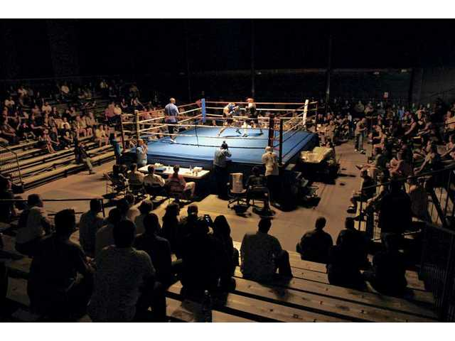A crowd watches four three-round bouts at the Western States Police and Fire Games held on a soundstage at Santa Clarita Studios on Tuesday evening.