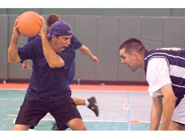 California Highway Patrol officer John Lutz, left, gets ready to attack a player from the Ada County sheriff's team of Boise, Idaho during the dodgeball tournament at the Western States Police & Fire Games Tuesday at the Santa Clarita Sports Complex.