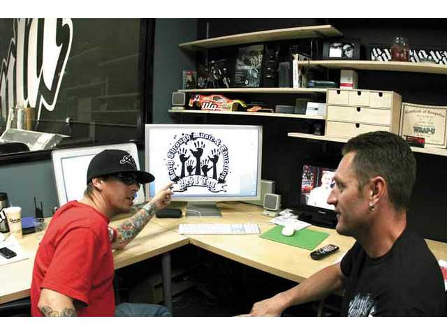NLA principals Jason Levy (left) and Jason Curtis finalize the design for the new Yes I Can T-shirts to be sold at Vans Warped Tour stops in Pomona and Ventura this weekend, and Los Angeles Aug. 17.
