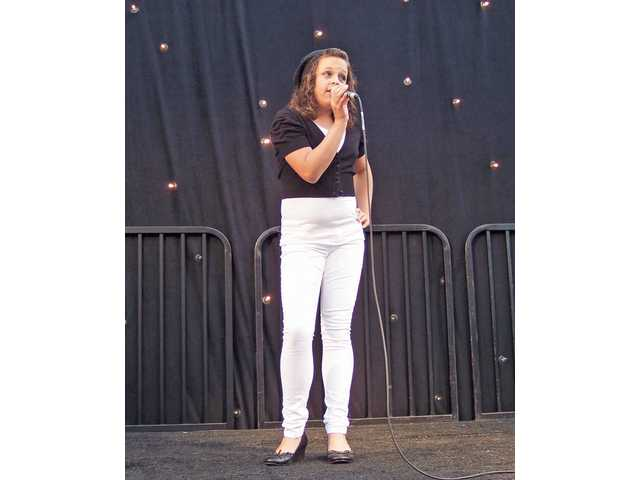 Caitie Acree, winner of the Sierra Vista Club's talent show, sings during dinner.