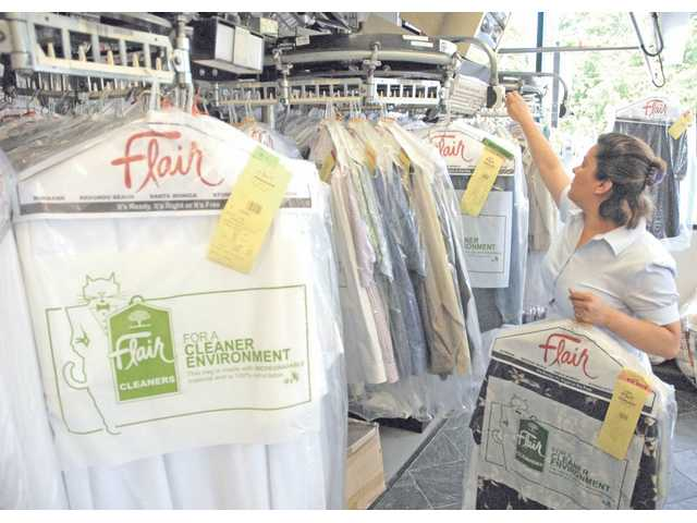 Flair Cleaners manager Maria Trejos pulls clean clothes from the rack.  Flair Cleaners offers free dry cleaning on Wednesdays for out-of-work customers with a recent unemployment pay stub.