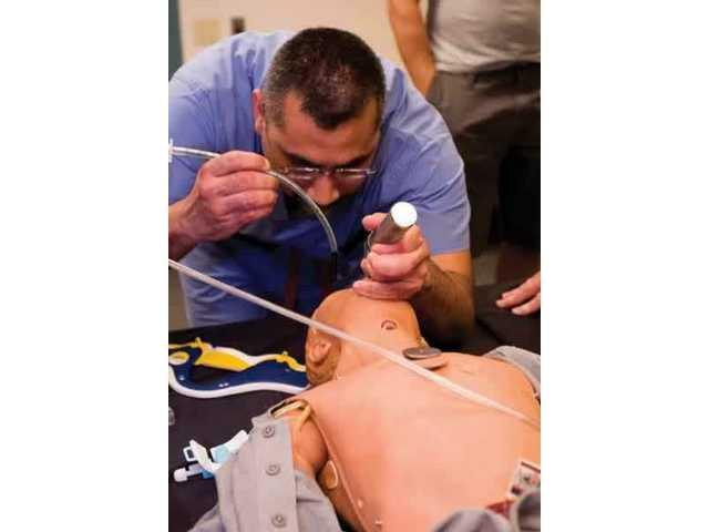 Dr. Edgar Enriquez of Henry Mayo Newhall Memorial Hospital works with CJ, the Medi HPS mannequin, during a joint training exercise done with first responders and the Homeland Security Department. Enriquez uses a laryngoscope to insert an endotracheal tube down CJ's  throat.