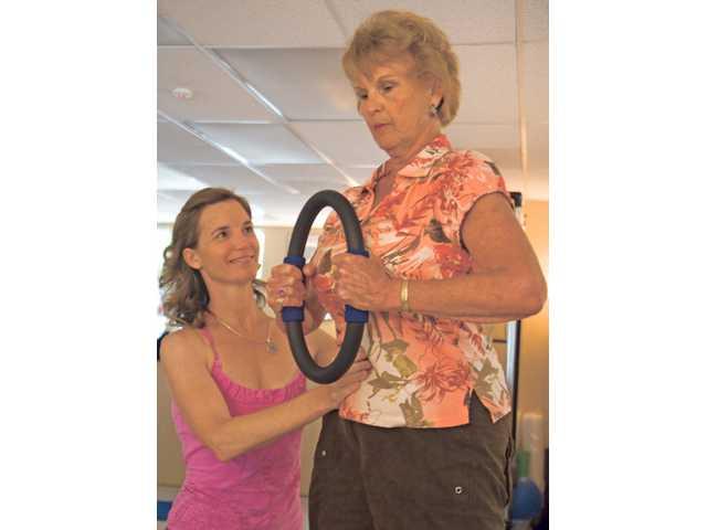 Pilates instructor Karena Thek Lineback helps her mother Regina Thek do the >>>>> standing move on the reformer machine in her Newhall pilates gym.