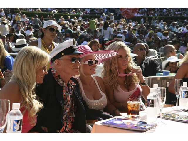"Playboy Jazz Festival godfather Hugh Hefner soaks up the rays and music in a front-row box at the Bowl, accompanied by ""Girls Next Door"" (from left) Bridget, Holly and Kendra."