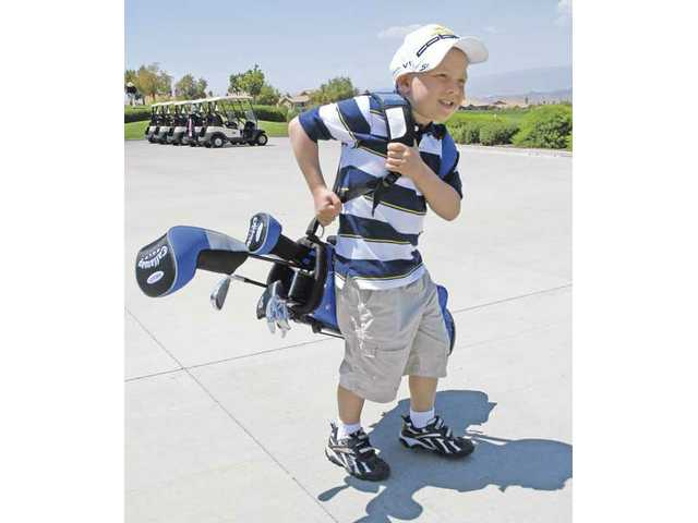 Tyler Cordova, 6, carries a set of clubs to the driving range at the Tournament Player's Club golf course in Valencia.