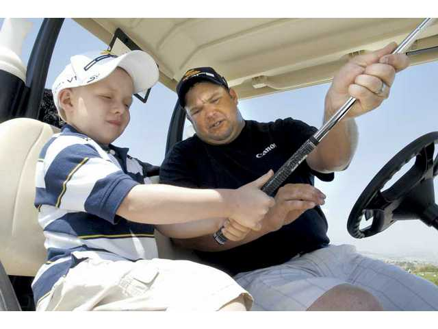 Tyler Cordova, 6, left, gets some tips on his grip from PGA Tour Pro golfer Jason Gore who stopped by to meet Tyler at Tournament Players Club golf course where the 10th annual Hoefflin Foundation Golf Classic will be held.