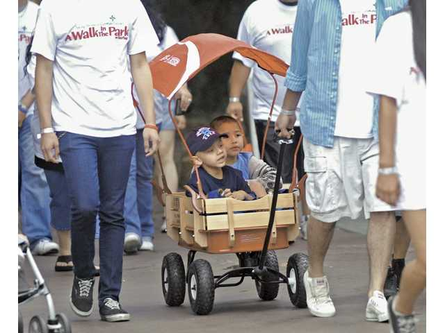 Andrew Guzman, left, and his cousin Matthew Heath catch a ride in a wagon as about 300 people participate in the walk.